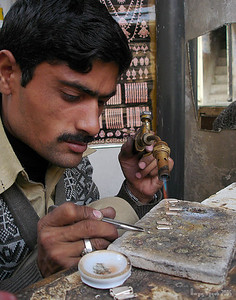 A crafts man making jewelery